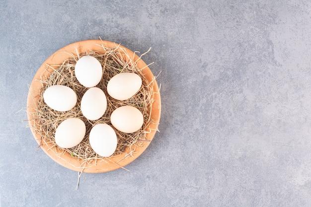 신선한 원시 흰색 닭고기 달걀은 돌 테이블에 배치됩니다.