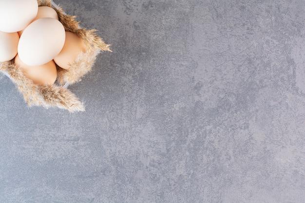 밀 귀를 가진 신선한 원시 흰색 닭고기 달걀은 돌 테이블에 배치됩니다.
