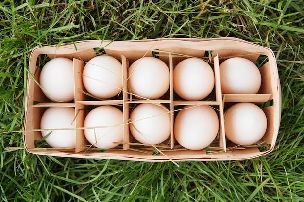 Fresh raw white chicken eggs in a wooden box on green grass