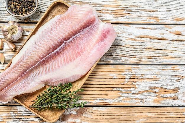 Свежее сырое филе белой рыбы сома со специями. белый деревянный фон