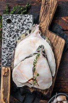 Fresh raw wolffish o wolf fish steak on a butcher board. dark wooden background. top view.