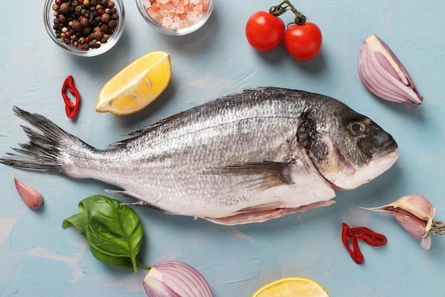 水色のテーブルの上で、バジル、レモン、塩、コショウ、チェリートマト、ニンニクなどの材料と調味料を使って生の魚のドラドを調理する準備ができています。上から見る