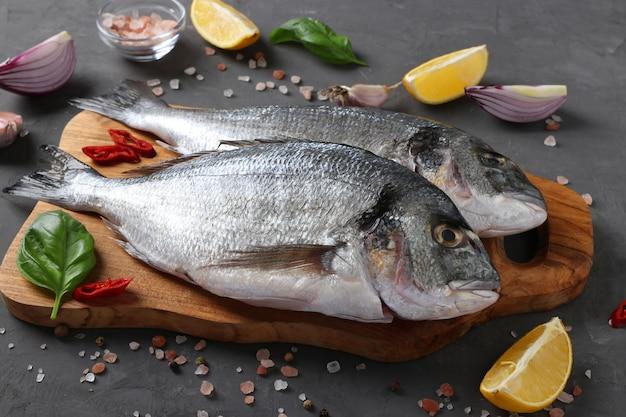 暗いテーブルの上の木の板にバジル、レモン、塩、コショウ、赤玉ねぎ、ニンニクなどの材料と調味料を使って生の魚のドラドを調理する準備ができています。閉じる
