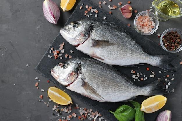Свежая, готовая к приготовлению сырая рыба дорадо с ингредиентами и приправами, такими как базилик, лимон, соль, перец, красный лук и оливковое масло на темной поверхности, вид сверху