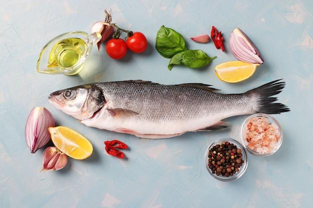Свежий, готовый к приготовлению сырой морской окунь с такими ингредиентами и приправами, как базилик, лимон, соль, перец, помидоры черри и чеснок, на голубой поверхности