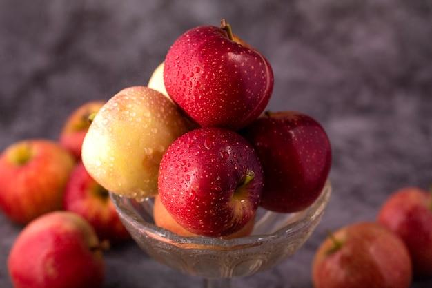 水滴とガラスのボウルに新鮮な赤と緑のリンゴ。