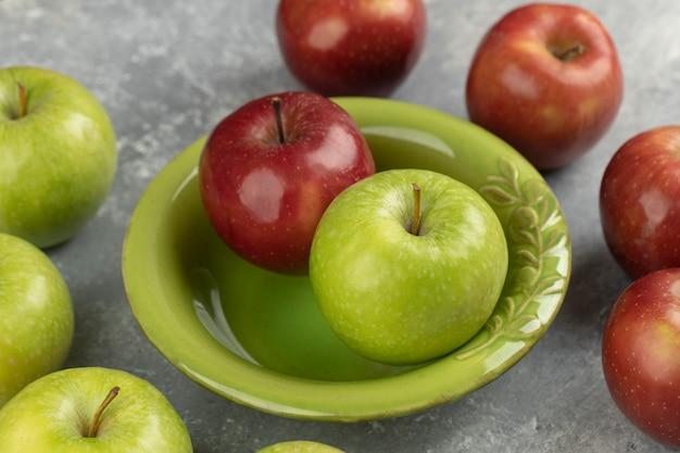 Свежие красные и зеленые яблоки в зеленой миске на мраморе.