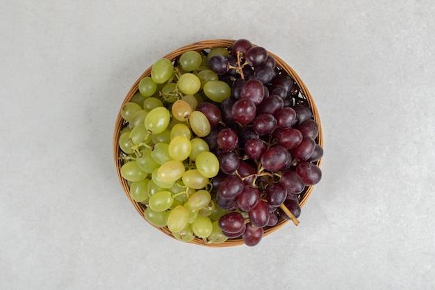 木製のバスケットに新鮮な赤と緑のブドウ