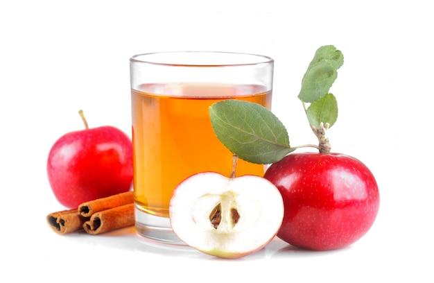 新鮮な赤いリンゴとシナモンの横にあるジュース