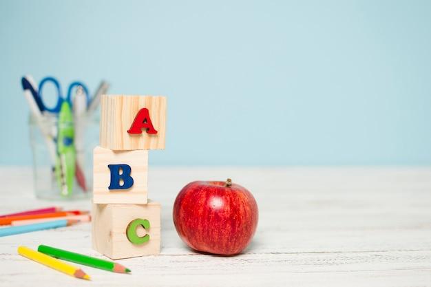 Свежее красное яблоко и школьные принадлежности