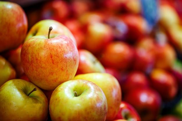 Fresh red apple fruits on shelves in supermarket