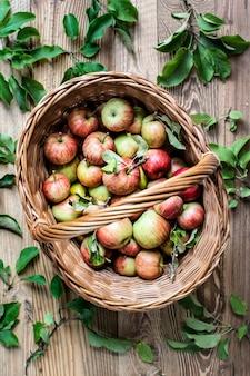 木製のテーブルの上のバスケットに新鮮な赤いリンゴ