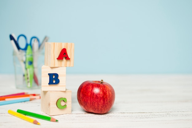 Fresh red apple and school supplies