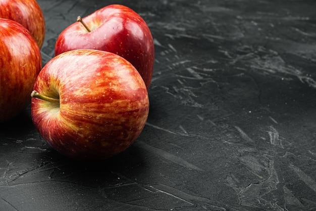 검은색 돌 테이블 배경에 있는 신선한 빨간 사과 세트, 텍스트 복사 공간
