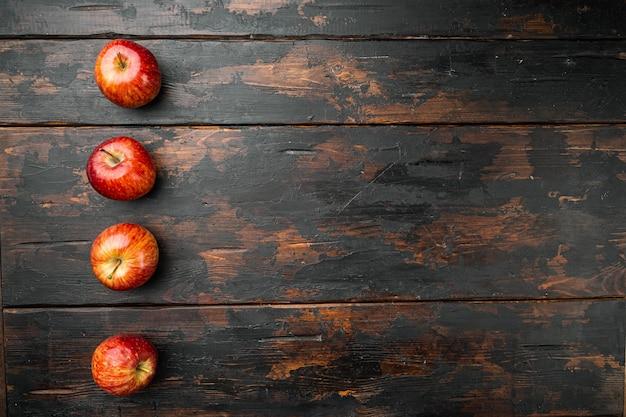 오래된 어두운 나무 테이블 배경에 있는 신선한 빨간 사과 세트, 텍스트 복사 공간이 있는 평면도
