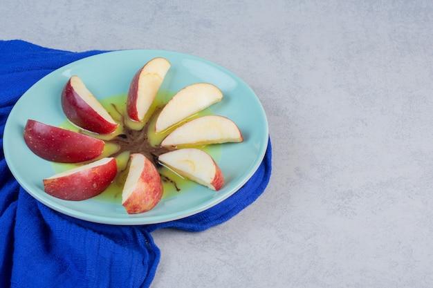 신선한 빨간 사과. 파란색 접시에 조각입니다.