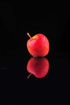 黒の背景に水滴と新鮮な赤いリンゴ