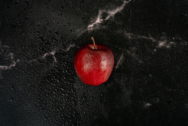 Fresh red apple with drops of water lies on a black marble, full of water spray droplets. top view flat lay composition.