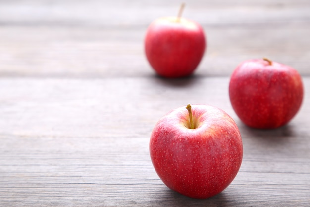 Fresh red apples on a grey wooden background