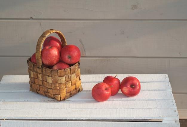 Свежие красные яблоки в винтажной плетеной корзине на белой коробке на сером стенном фоне