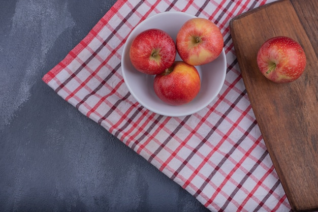 Свежие красные яблоки в белом шаре со скатертью.