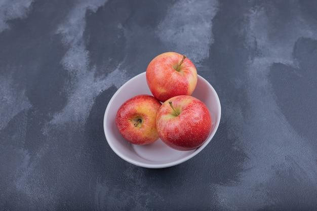 白いボウルに新鮮な赤いリンゴ。
