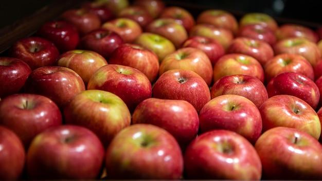 시장 카운터에 신선한 빨간 사과입니다. 식료품 선반에 있는 판지 상자에 있는 사과. 슈퍼마켓에서 과일의 보기를 닫습니다. 건강한 식생활과 채식주의