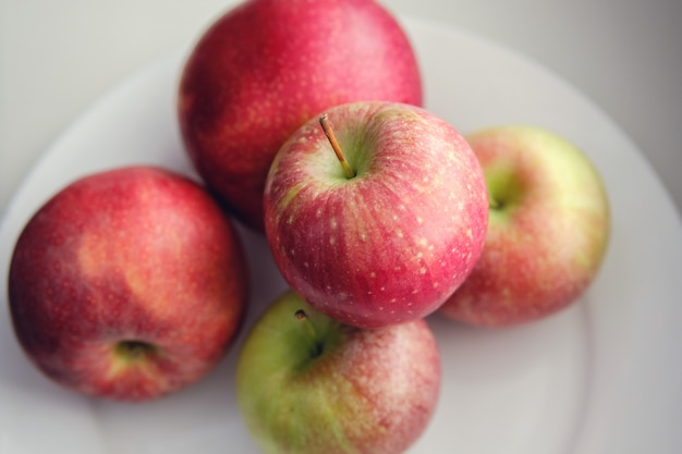 Fresh red apples on a white plate. healthy diet.