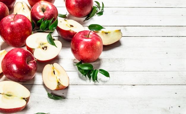 白い木製のテーブルの上に葉を持つ新鮮な赤いリンゴ。