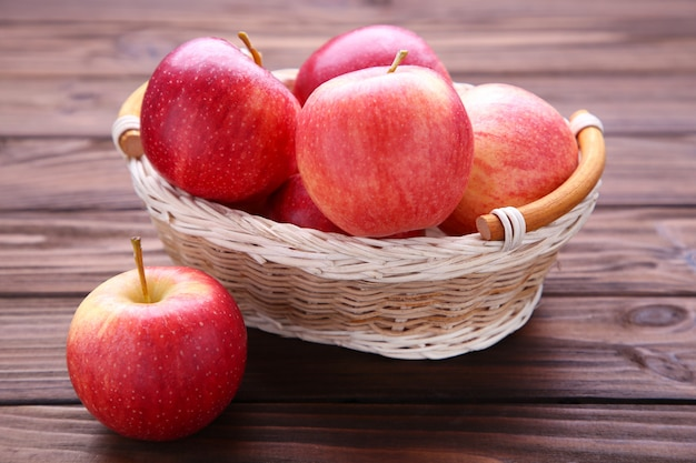 Fresh red apples on wooden background.