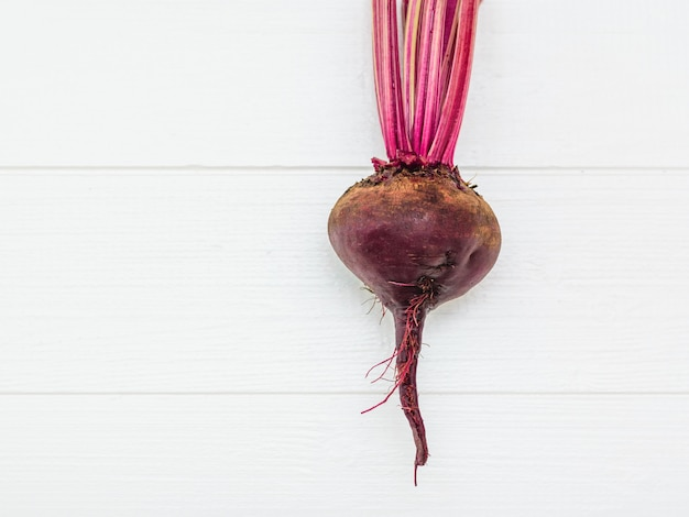 Fresh red beetroot on a white wooden table.