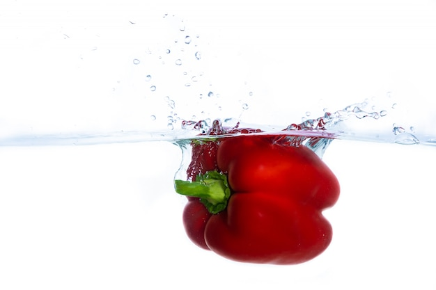 Fresh red bell pepper falls in water