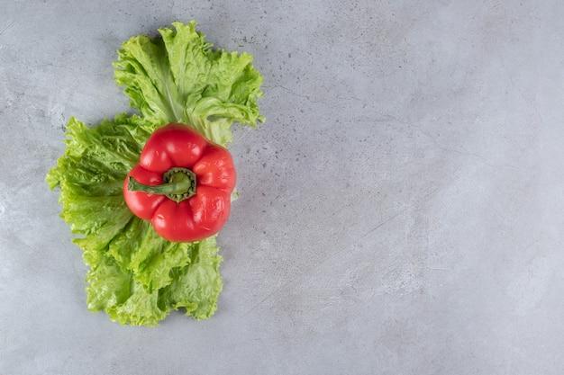 Peperone rosso fresco con lattuga su sfondo grigio. foto di alta qualità