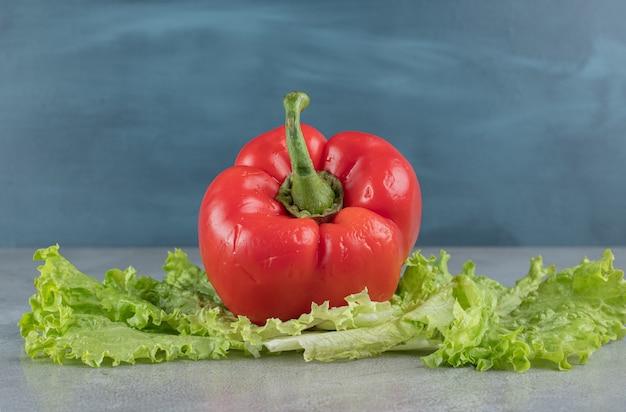 Свежий красный перец с салатом на сером фоне. фото высокого качества