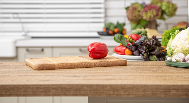 Fresh red bell pepper on a wooden plank against the background of a kitchen interior.