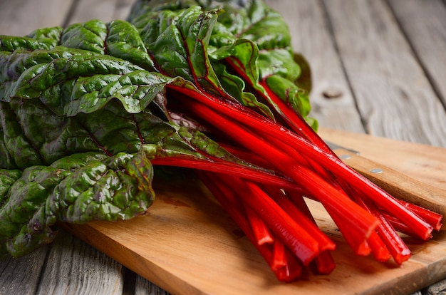 Fresh red chard leaves on wooden background.