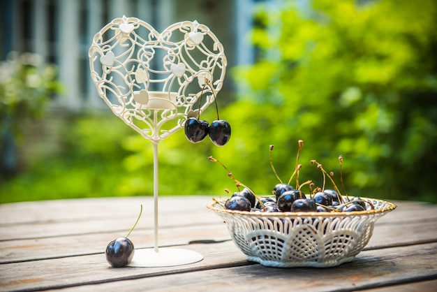 Fresh red cherries berries in a white plate on the wooden table with candlestick in the shape of the heart