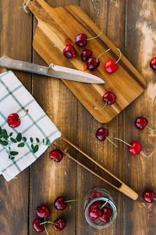 Fresh red cherries and knife on wooden cutting board