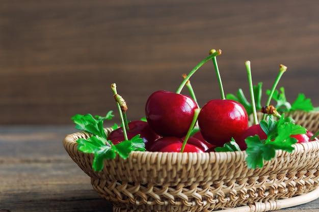 나무 바구니에 신선한 빨간 체리 복사 공간 측면보기에서 나무 테이블에 넣어. 프리미엄 사진