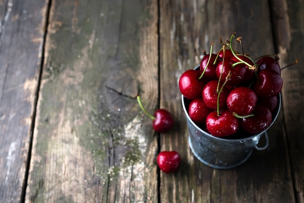 Fresh red cherries on wooden table with water drops