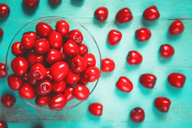 Fresh red cherry in a bowl on an old painted wooden table as a bright colorful summer background