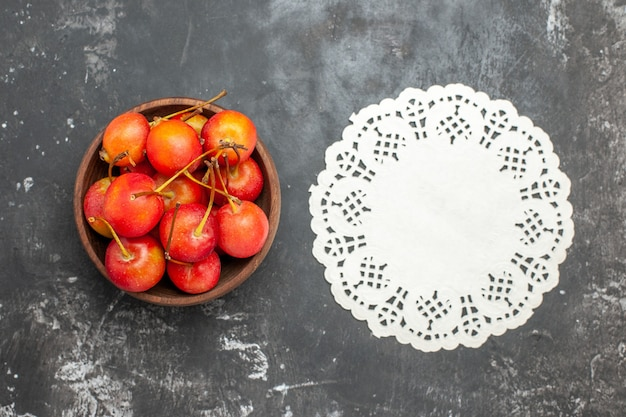 Fresh red cherry fruit in a bowl on gray background