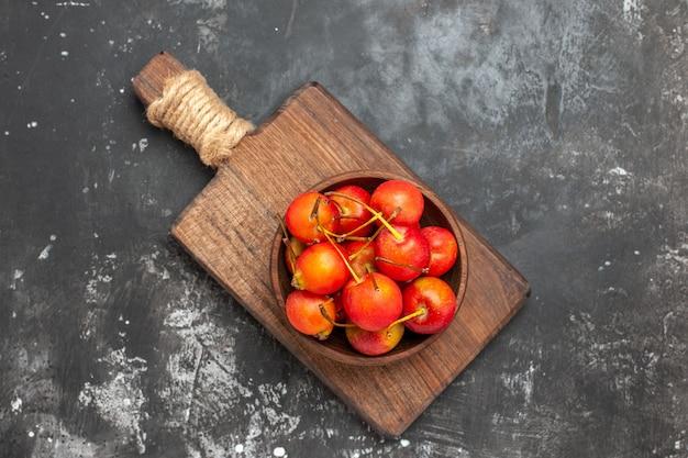 灰色の背景のボウルに新鮮な赤い桜の果実