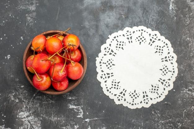 회색 배경에 그릇에 신선한 빨간 체리 과일