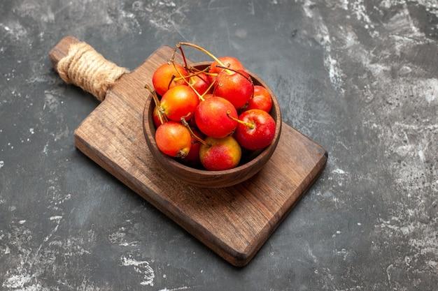 Свежие красные вишни в миске на сером фоне