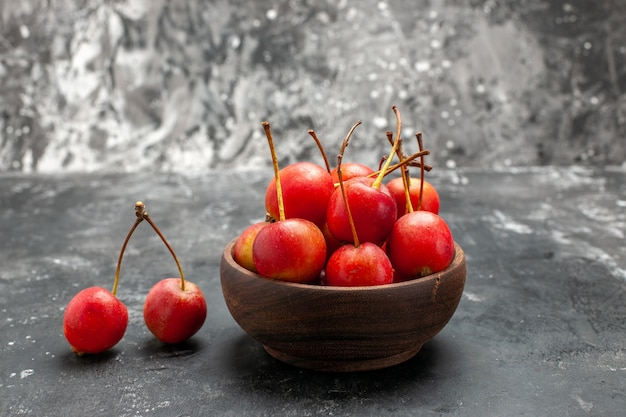 Свежие красные вишни в коричневой миске на сером фоне