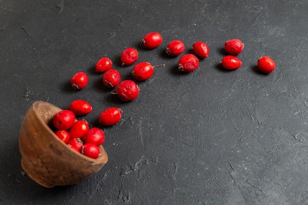 灰色の背景に茶色のボウルに新鮮な赤い桜の果実