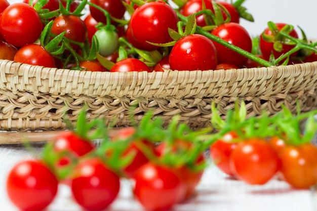 Fresh red cherry tomato on wood basket, selective focus on background.