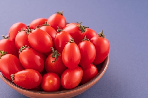 파란색 배경에 고립 된 나무 그릇에 신선한 빨간 체리 토마토를 닫습니다.
