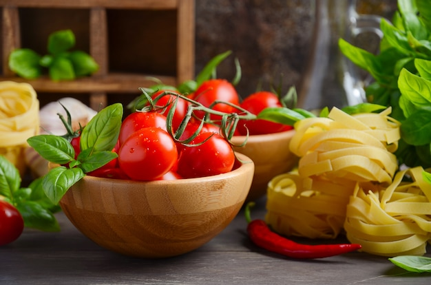 Fresh red cherry tomatoes with raw pasta, basil, chili pepper and garlic for italian food.